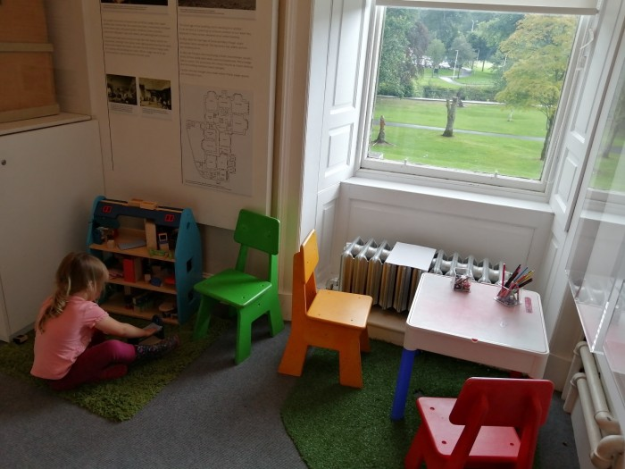 Girl playing dolls house small table and chairs