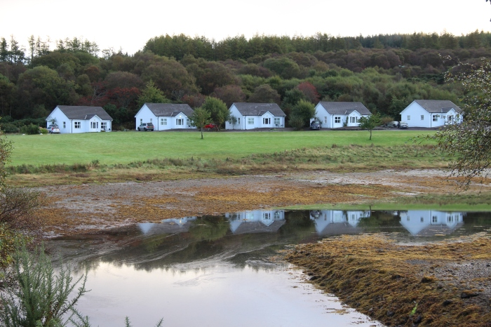 body of water reflections of white cottages