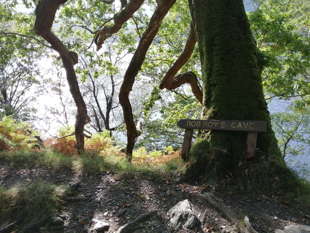 west highland way, scotland, trees, rob roys cave, sign