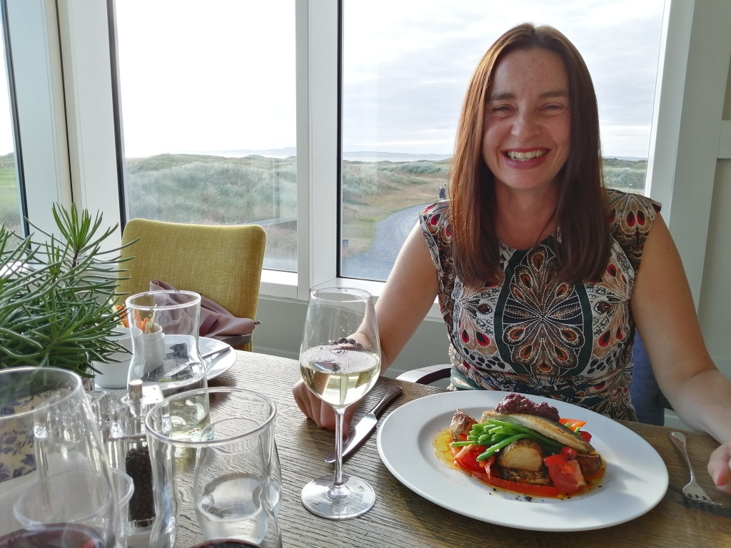 lady smiling, wine, food, view golf course, machrie hotel, islay, scotland