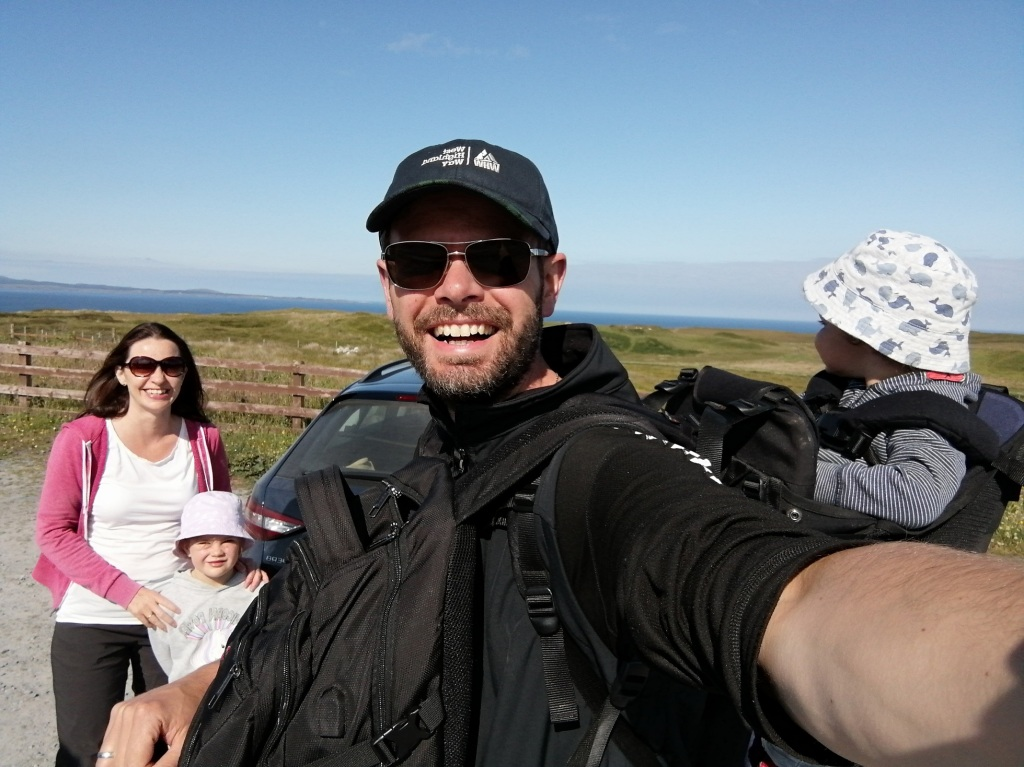 guy smiling, baby carrier, sunglasses, blue skies, islay, scotland