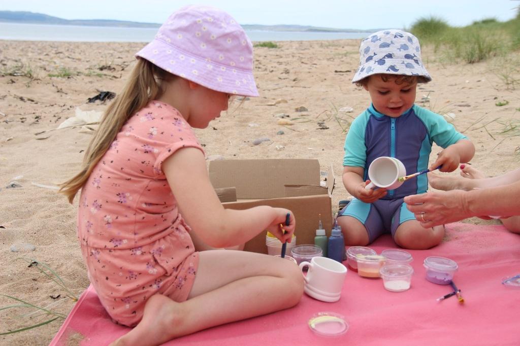 beach, child in swim suite, smiling child, sandy beach, ceramics, painting, persabus pottery, machrie, laggan bay, islay, scotland